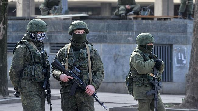"""Unidentified armed men patrol in front of the Crimean Parliament in Simferopol on March 01, 2014. Pro-Russian forces tightened their grip on Crimea on Saturday as the Kremlin vowed to help restore calm on the restive Ukrainian peninsula and Washington warned of """"costs"""" to Moscow should it order in troops. Dozens of armed men in full combat gear were patrolling the streets of Crimea's capital of Simferopol a day after similar gunmen seized control over airports and government buildings in the Ukrainian territory where the majority of the population is Russian and where one of Moscow's main fleets is based. AFP PHOTO/ GENYA SAVILOV"""
